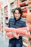 Man holding a roll of wallpaper in the store Stock Photo