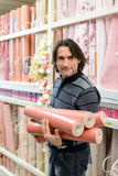 Man holding a roll of wallpaper in the store Stock Image