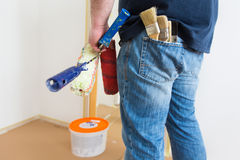 Man holding rollers and brushes stock photo