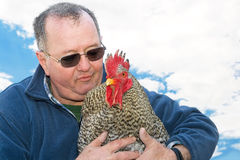 Man holding a rooster in his arms Stock Photography