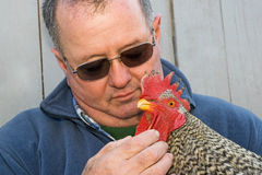 Man holding a rooster in his arms Stock Images