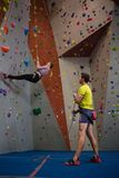 Man holding rope looking at athlete climbing wall in fitness club. Man holding rope looking at female athlete climbing wall in fitness club royalty free stock photography