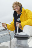 Man holding rope of winch and helm on sailboat Stock Images