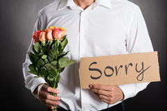 Man Holding Roses And Text Sorry Written On Cardboard Royalty Free Stock Image