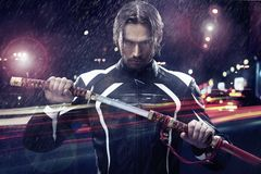 Man holding a samurai sword. On a night city street Royalty Free Stock Photos
