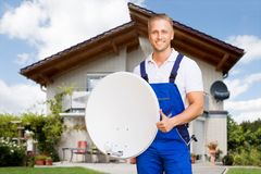 Man Holding Satellite Dish Showing Thumb Up Sign. Smiling Young Man Standing Outside The House Holding Satellite Dish Showing Thumb Up Sign royalty free stock images