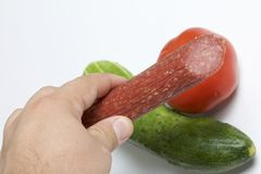 The man is holding a sausage stick in his hands. Next to the table is a cucumber and tomato. Stock Photo