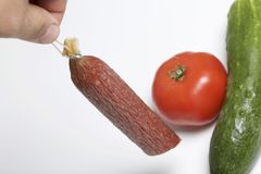 The man is holding a sausage stick in his hands. Next to the table is a cucumber and tomato. Stock Photos