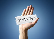 Man holding a scrap of paper with - IBAN / BIC. Man holding up a scrap of white paper with the words - IBAN / BIC - in script, close up of his hand on a blue Stock Photography