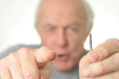 Man holding a screw and pointing to camera. Royalty Free Stock Images