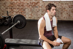 Man holding shaker bottle while sitting. At the gym Stock Photography
