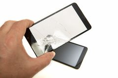 Man holding a shattered smartphone screen. In his hand with the mobile phone visible below in a close up view showing the damage to the glass. high quality Stock Photos