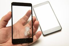 Man holding a shattered smartphone screen. In his hand with the mobile phone visible below in a close up view showing the damage to the glass. high quality Royalty Free Stock Images
