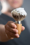 Man is holding a Shaving Brush in the Hand Royalty Free Stock Photography