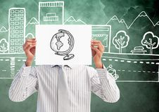 Man holding sheet of paper with drawn globe in front of his face and graphics in background Stock Photo
