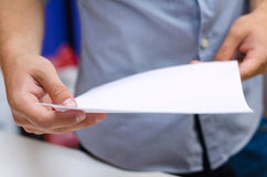 Man holding a sheet of paper. Man holding a white sheet of paper Stock Photos