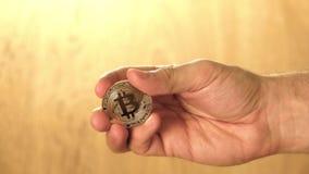 Man holding shiny bitcoin in his hand. Man holding shiny bitcoin in hand stock video