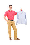Man holding a shirt on a hanger Royalty Free Stock Photography