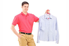 Man holding a shirt on a hanger. Isolated on white background Royalty Free Stock Photo