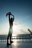 Man holding a shirt over his head against sea sunset Stock Photos
