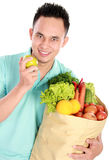 Man holding shopping bag full of groceries. Smiling young man holding shopping bag full of groceries isolated against white background Royalty Free Stock Image