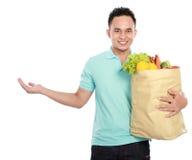 Man holding shopping bag full of groceries presenting. Smiling young man holding shopping bag full of groceries presenting copyspace Royalty Free Stock Image