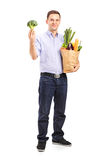 Man holding a shopping bag with products Stock Image