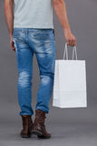 Man holding shopping bag. Rear view of man holding a white shopping bag against grey background royalty free stock image