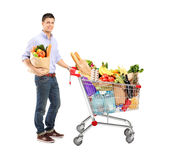 Man holding a shopping bag and shopping cart. Full length portrait of a man holding a shopping bag and shopping cart on white background Royalty Free Stock Photos