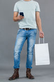 Man holding shopping bag and using mobile phone. Low section of man holding shopping bag and using mobile phone against grey background Royalty Free Stock Photo