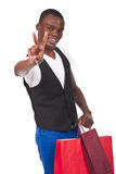 Man holding shopping bags and doing victory sign Royalty Free Stock Images