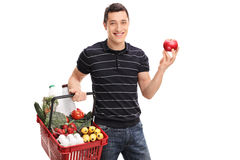 Man holding a shopping basket and an apple Stock Photo