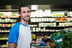 Man holding shopping basket in supermarket Stock Photos