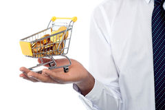 Man holding a shopping cart filled with gold coins Stock Photos