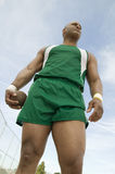 Man Holding Shot Put Against Sky. Low angle view of male athlete holding metal ball against sky Royalty Free Stock Photo