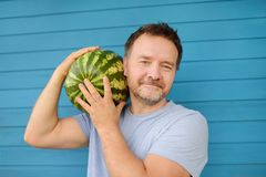Man holding at the shoulder big watermelon stock photo