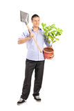 Man holding a shovel and a plant Stock Photo