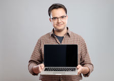 Man holding and showing laptop computer royalty free stock photos