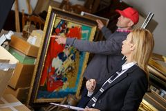 Man holding and showing painting to auctioneer before auction. Man holding and showing a painting to auctioneer before auction Royalty Free Stock Photography