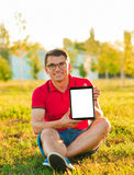 Man holding and shows touch screen tablet pc. Young man using tablet computer on autumn  park. Man holding and shows touch screen tablet pc with blank screen Royalty Free Stock Photography