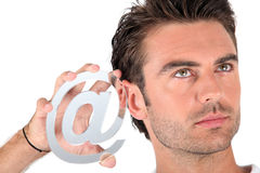Man holding an @ sign Royalty Free Stock Images