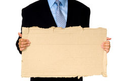 Man holding sign. Man in blue business suit holding a cardboard sign- lots of copy space, unemployed  business man- asking for work Royalty Free Stock Image
