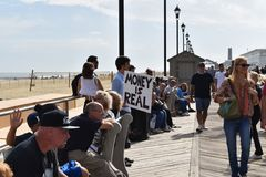 Asbury Park, New Jersey - October 7, 2017: This man tried to calm fears ot the 10th annual Asbury Park Zombie Walk. Man holding sign on boardwalk that says, ` royalty free stock photos