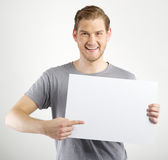 Man holding sign. Smiling young man holding blank sign in hands royalty free stock photography