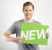 Man holding sign. Smiling young man holding sign in hands Stock Photo