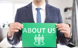 Man holding sign with about us text and drawing stock images