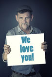 Man holding sign with the words We Love You Royalty Free Stock Photos