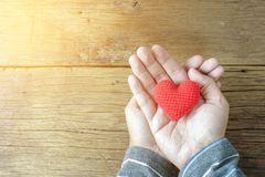 Man holding a single red heart on wooden. Table Royalty Free Stock Photos