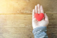 Man holding a single red heart on wooden background. Man holding a single red heart on wooden table Royalty Free Stock Photos
