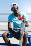Man holding skateboard at a boardwalk. On a sunny day Stock Images